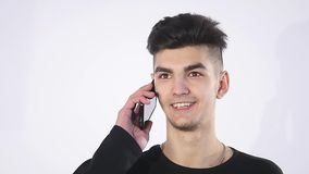 Puzzled confused young man speaking to cell phone.Man portrait thinking and speaking to phone stock video