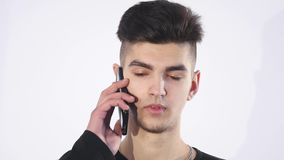Puzzled confused young man speaking to cell phone.Man portrait thinking and speaking to phone stock footage