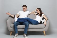 Puzzled couple woman man football fans cheer up support favorite team with soccer ball, spreading hands isolated on grey. Puzzled couple women men football fans royalty free stock images