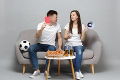 Puzzled couple woman man football fans cheer up support favorite team, swearing, holding megaphone, red card isolated on. Puzzled couple women men football fans stock photo