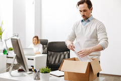 Puzzled employee gathering the box and leaving the company Royalty Free Stock Image