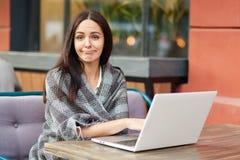 Puzzled ermüdete weiblichen Freiberufler macht die on-line-Forschung von den Informationen, eingewickelt in der warmen Bettdecke, stockfotos