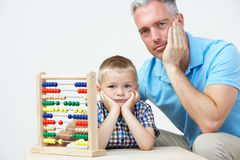 Puzzled Father And Son Looking Abacus Royalty Free Stock Photos