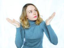 A puzzled girl is shrugging. An emotional puzzled girl wearing grey sweater is shrugging on a white background Stock Photography