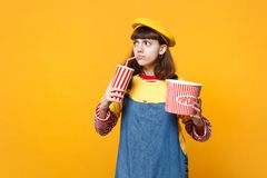 Puzzled girl teenager in french beret, denim sundress hold plastic cup of cola or soda, bucket of popcorn isolated on. Yellow background. People sincere stock photo