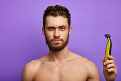 Puzzled handsome man looks embarrassed at electric shaver stock photography