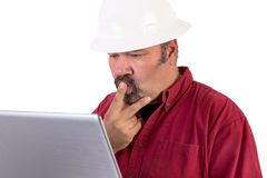 Puzzled Hardhat Worker. Hardhat worker working or surfing with his laptop, he has a puzzled look, he is wearing red shirt and isolated on white background, copy Stock Images