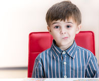 Puzzled little boy. At the table Royalty Free Stock Photos