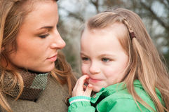 Puzzled little girl on mother's hands Stock Photos