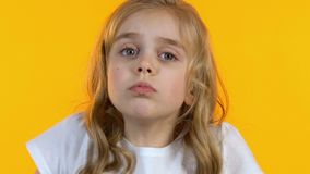 Puzzled little girl shrugging looking around, child cant make decision, close-up. Stock footage stock footage