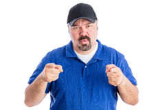 Puzzled man pointing at the camera. Puzzled middle-aged man with a goatee wearing a baseball cap pointing at the camera with a quizzical frown as he seeks Royalty Free Stock Photos