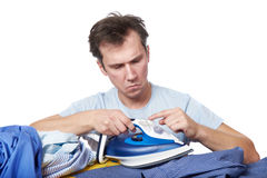 Puzzled man studying how to use an iron isolated white Stock Image