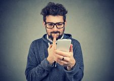 Puzzled man thinking what to reply to received text message on cell phone stock images