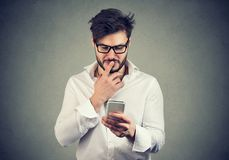 Puzzled man thinking what to reply to received text message on cell phone. On gray wall background. Face expression reaction body language stock photos