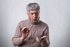 A puzzled mature man in brown sweater holding smartphone trying to understand how to switch it on. Troubled elderly man holding sm Royalty Free Stock Image