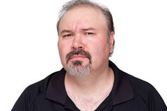 Puzzled middle-aged man with a goatee. Frowning and looking at the camera with a look of distrust isolated on white Stock Photography
