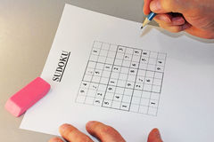 For Puzzled Minds. A Sudoku puzzle with hands working on the solution and a much needed eraser visible also Royalty Free Stock Photos