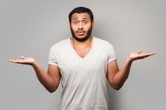 Puzzled mixed race man spreading his hands Royalty Free Stock Image