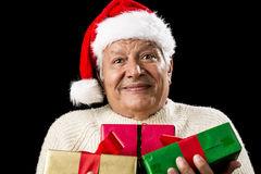 Puzzled Old Gentleman Carrying Three Wrapped Gifts. Friendly, but perplexed looking male pensioner with Santa Claus cap. He is carrying Christmas presents in Stock Image