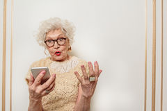 Puzzled old lady does not understand modern technology. What is that. Shocked senior woman is staring at mobile phone with confusion. She is standing and Royalty Free Stock Photo