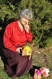 Puzzled, the old woman holds a lot of gifts Royalty Free Stock Photo