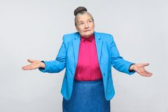 Puzzled old woman. Puzzled or confused old woman. Emotion and feelings handsome expressive grandmother with light blue suit and pink shirt standing with royalty free stock image