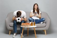Puzzled sad couple woman man football fans cheer up support favorite team with soccer ball using mobile phone isolated. Puzzled sad couple women men football royalty free stock images