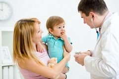 Puzzled or scared baby being checked by a doctor Royalty Free Stock Images