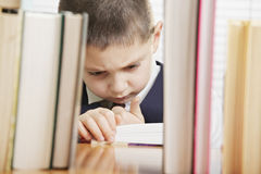 Puzzled schoolboy reading book Stock Photography
