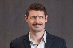 Puzzled som ser mannen med en kort mustasch Royaltyfri Fotografi