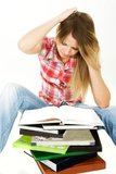Puzzled student girl with pile of books Stock Image