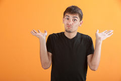 Puzzled Teen. Puzzled young Latino teen on an orange background Stock Photo