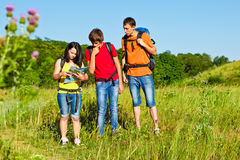 Puzzled teenagers looking into map. Puzzled hiking teenagers looking into map Royalty Free Stock Photos