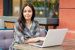 Puzzled tired female freelancer makes online research of information, wrapped in warm coverlet, poses against cafe interior. Attra. Ctive woman student studies Stock Photos