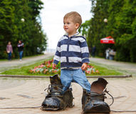 Puzzled two years old boy standing in giant boots. On the street Stock Images