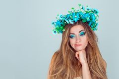 Puzzled upset young Woman with floral headband looking down royalty free stock photo