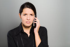 Puzzled woman chatting on her mobile. Puzzled beautiful young woman chatting on her mobile phone and looking at the camera with a confused expression and frown Stock Photo