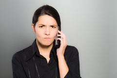 Puzzled woman chatting on her mobile. Puzzled beautiful young woman chatting on her mobile phone and looking at the camera with a confused expression and frown Royalty Free Stock Image