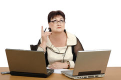 Puzzled woman in front of two laptops Stock Image