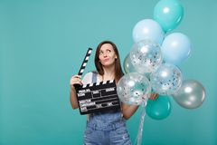 Puzzled woman looking up, holding classic black film making clapperboard, celebrating with colorful air balloons