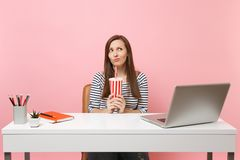 Puzzled woman in perplexity croaking thinking looking up holding plactic cup with cola, soda sit work at white desk with. Pc laptop isolated on pink background royalty free stock photo