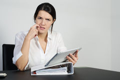 Puzzled woman thinking hard. And grimacing as she tries to find an answer to a problem posed on her handheld tablet computer stock images