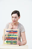 Puzzled Woman Using Abacus Stock Photo