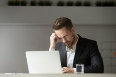 Puzzled young businessman looking at laptop screen at workplace. Stock Photos