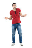 Puzzled young casual man in red t-shirt shrugging shoulders looking at camera. Full body length portrait isolated over white studio background Stock Images