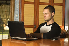 Puzzled young male surfing the web. Inside home Stock Image