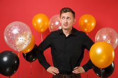 Puzzled young man in black classic shirt standing with arms akimbo on bright red background air balloons. Valentine`s. International Women`s Day, Happy New stock image