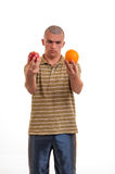 Puzzled young man confused, what to choice between an apple an an orange Royalty Free Stock Photos
