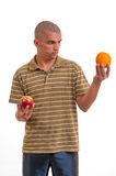 Puzzled young man confused, what to choice between an apple an an orange Royalty Free Stock Photography