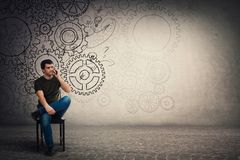 Puzzled young man sitting on chair talking on his smartphone, hard thinking serious guy with cogwheel gear brain stock photo